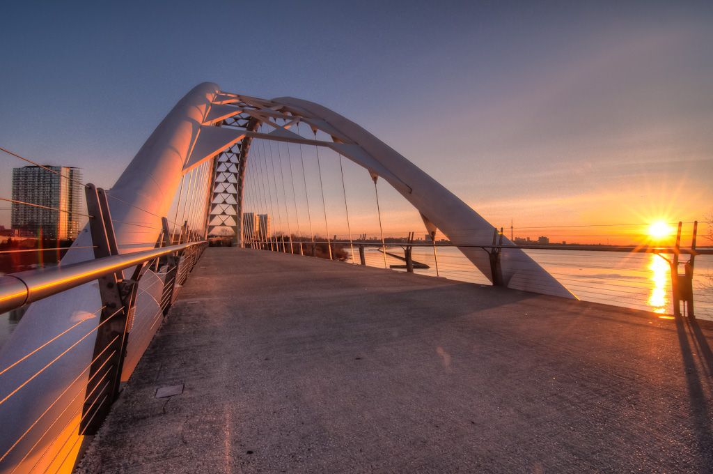 Humber Bay Arch Bridge at sunrise with a view of the CN Tower across the water