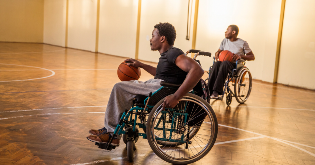 2 men in wheelchairs playing basketball.