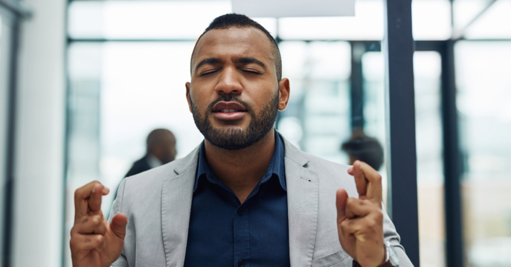 Man with eyes closed crossing fingers in an office space.