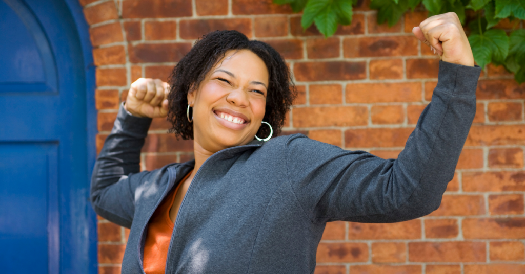 Woman smiling posed with fists in the air.