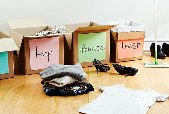 """Boxes to declutter labelled """"keep"""", """"donate"""", and """"trash"""" with clothes and shoes on the floor."""