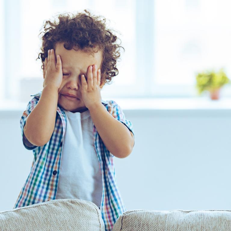 Toddler upset rubbing his eyes