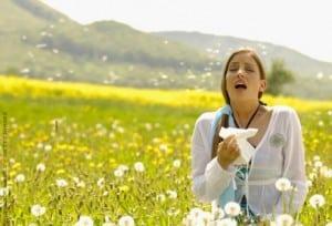 getty_woman_sneezing_in_flowering_meadow