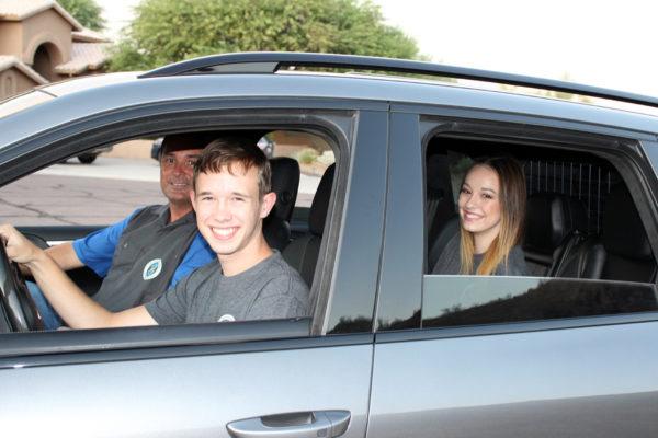 family smiling in car