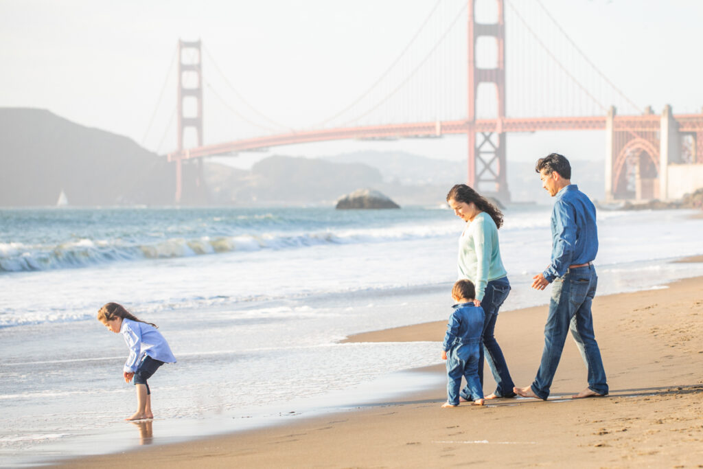 family playing in the waves