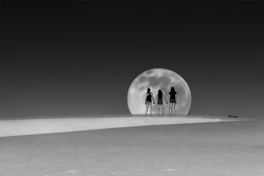Full Blue Moon rising over three girls holding hands at White Sands NM.