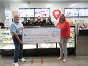 Two people pose with a large check with 5 other people in the background.