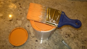 orange paint can and wooster shortcut brush on counter