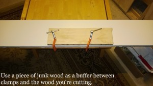 using a piece of junk wood as a buffer between clamps and the wood you're cutting