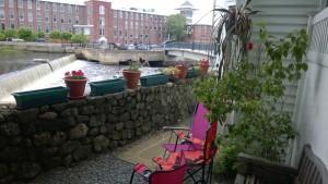back yard of condo with views of the ipswich river, waterfall, riverwalk bridge and ebsco