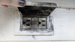 burnt outdoor electrical outlet after it shot flames at jim