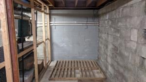 two coats of grey drylok waterproofing sealant on the basement wall