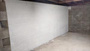 two coats of white drylok waterproofing sealant on the basement wall