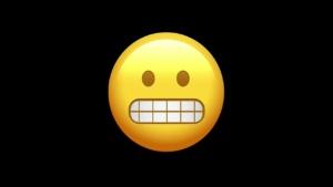grimacing emoji on black background