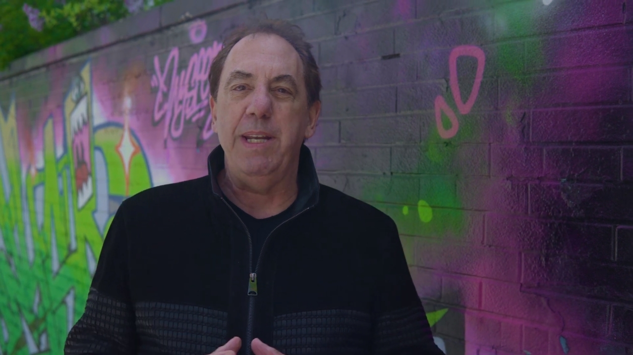 Image of Doug Keeley Speaks standing in front of a graffiti wall talking about the power of corporate storytelling