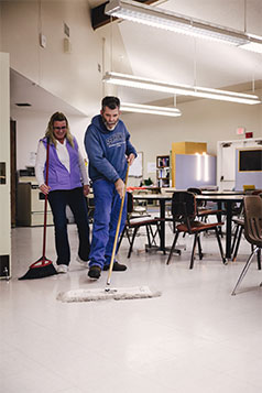 Staff teaching client to dust mop.