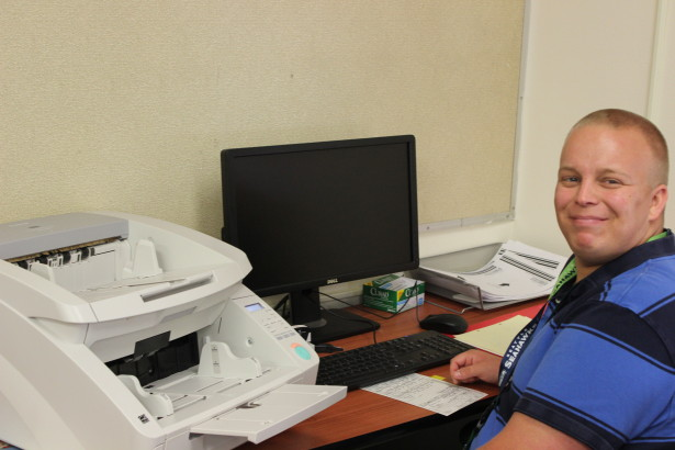 Jacob pictured at his work station scanning documents for the Yakima Count Courthouse.