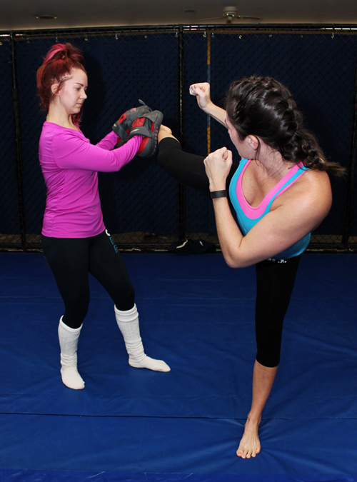 Women's Self-Defense class with students practicing high kicks