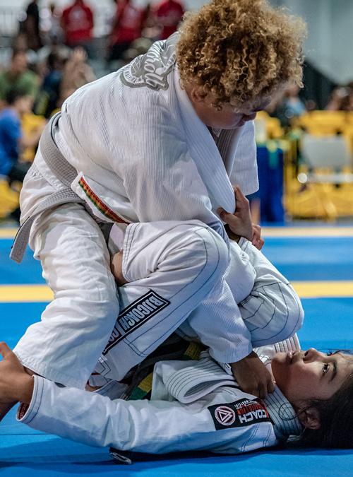 Kid applying a Brazilian Jiu-jitsu sweep on opponent at the IBJJF American National