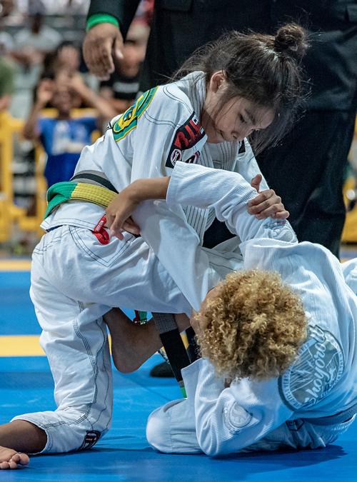 Kid's rolling against each other at Brazilian Jiu-jitsu tournament