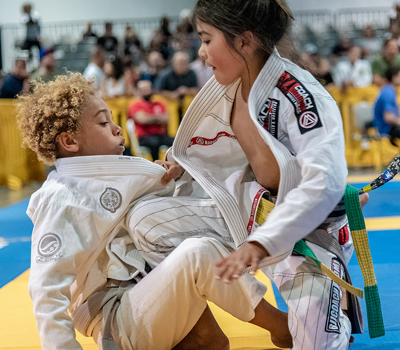 Kid BJJ martial artist passing the guard of an opponent