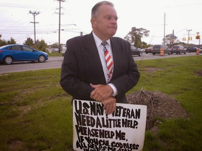 """Man in his 50s or 60s dressed in a suit holding a sign reading """"U.S. Navy Veteran. Need a little help. Please help me."""