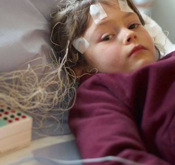 Child wearing traditional wired EEG headset