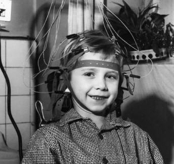 Child wearing old wired EEG headset