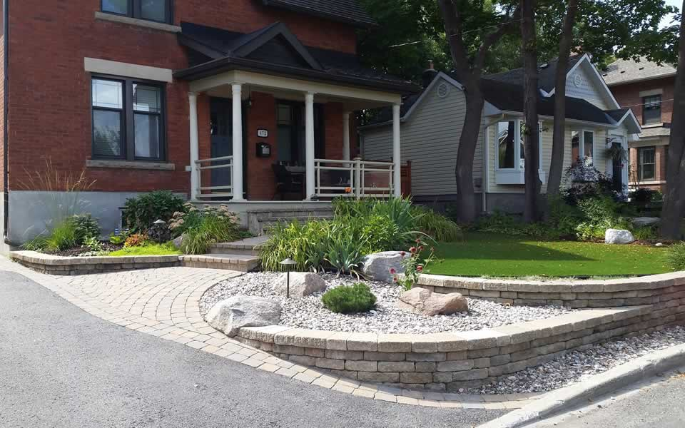 Terraced front yard with Synthetic lawn designed by Rhonda Derue, installation Yards Unlimited Landscaping, Inc   Retained levels of sloped front entrance