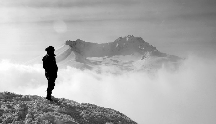 woman looking out at a mountain range needing confidence