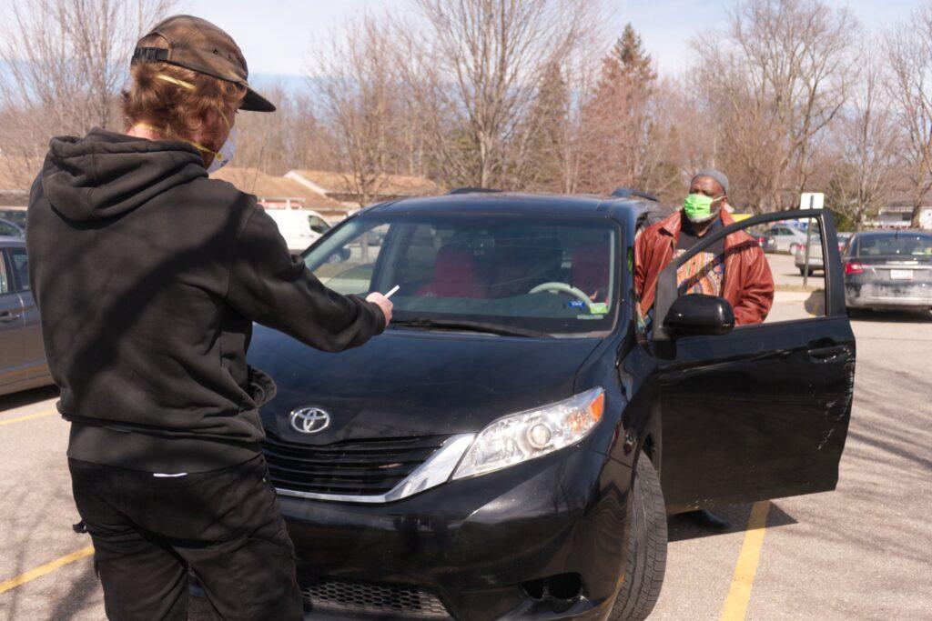 Volunteer helps attendee diagnose their headlights.