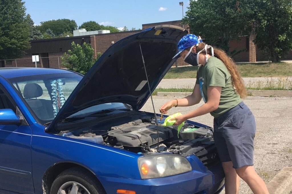 Mechanic checks a car's oil level.