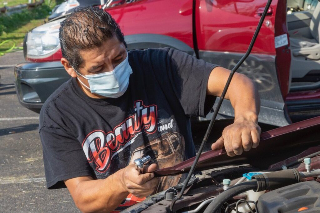 Mechanic detaches a car part.