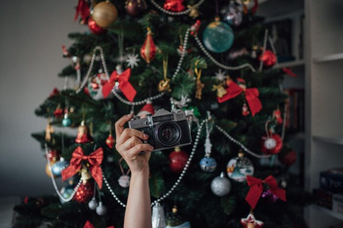 Photo of a hand holding up a camera in front of a Christmas Tree.