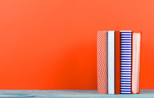 Image of 5 books displayed in front of a bright orange wall