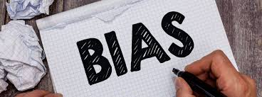The word BIAS written in large black letters by a hand holding a pen on notebook paper