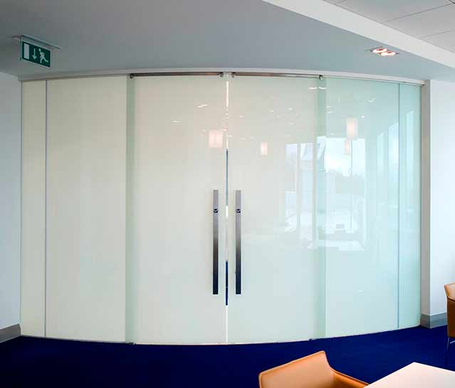 Brisk Architectural Smart glass partition system.  The image shows a curved partitions with double sliding glass doors.