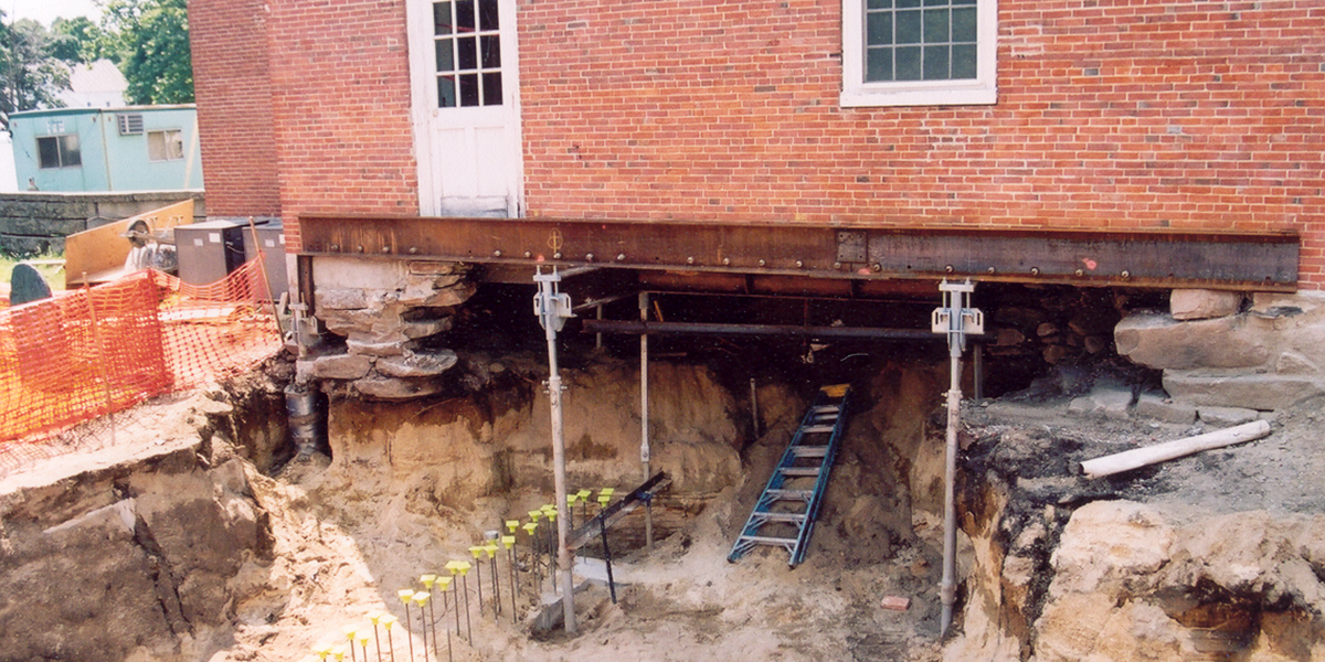 Town hall foundation repair with helical pile underpinnings by Solid Earth Technologies