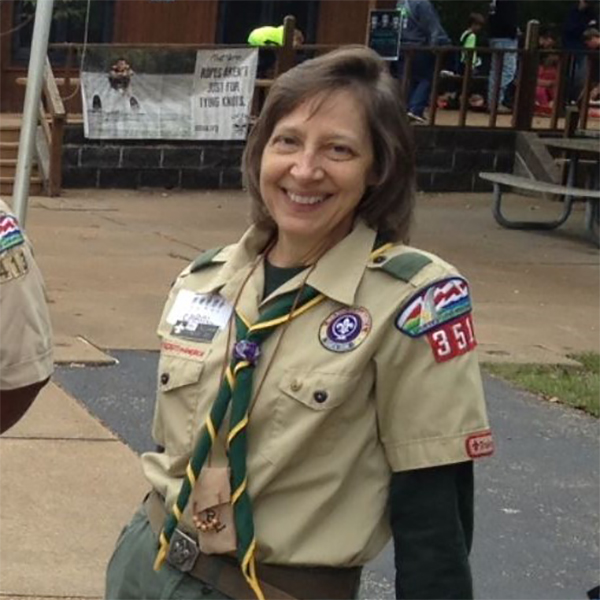 Carol smiles for the camera, wearing a scouts uniform