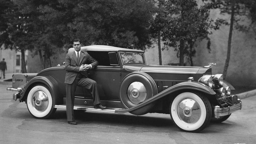Clark Gable 24th April 1933: American screen star Clark Gable(1901-1960), who became known as the 'King of Hollywood', poses next to his luxurious 1932 Packard.