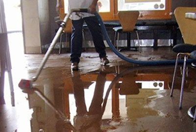 Water Damage Restoration in Philadelphia, Pa - Technician Cleaning Up Water Image