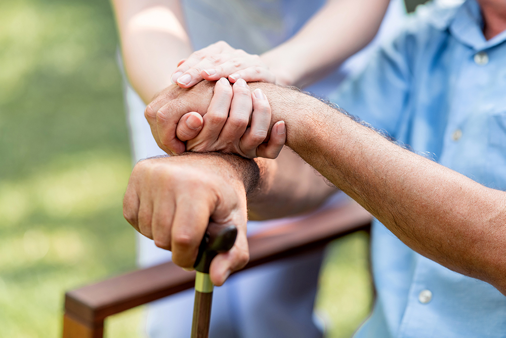 cna caregiver and senior holding hands closeup