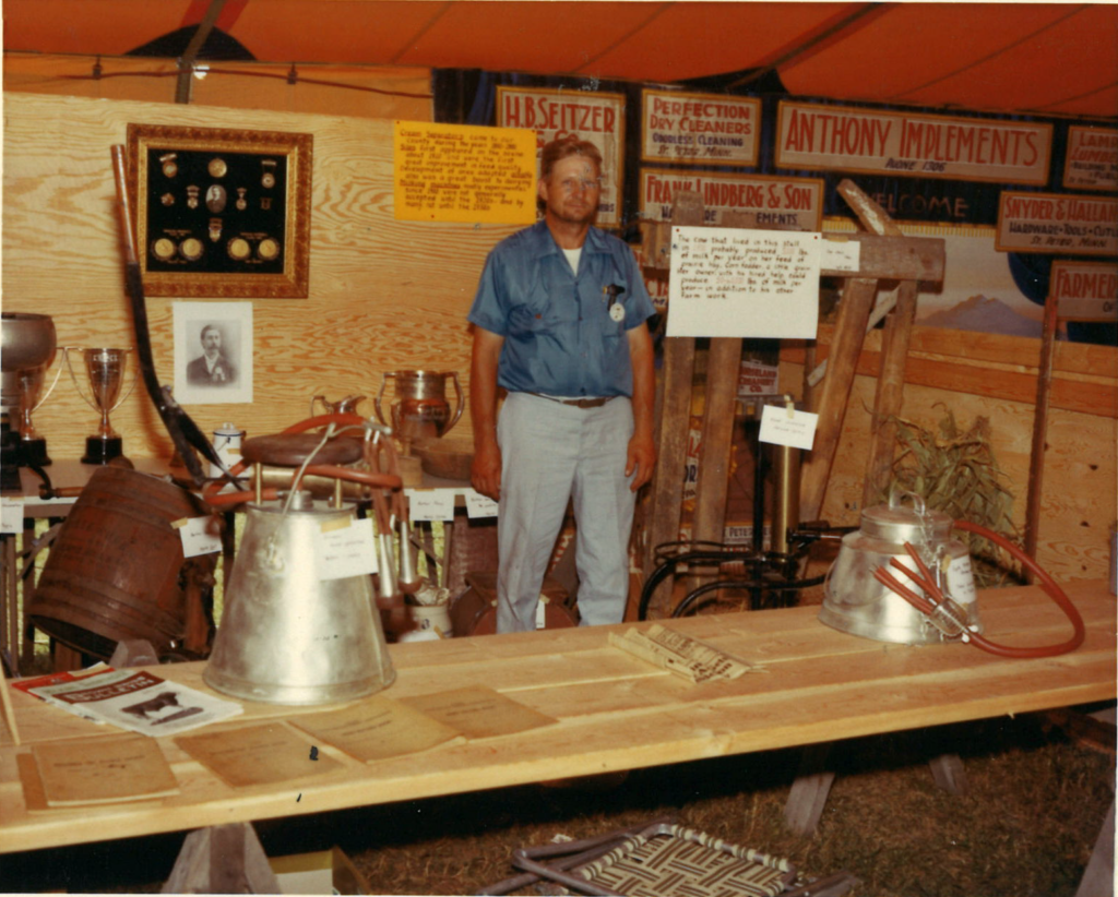 Color photo of a man standing inside a fair booth in 1971