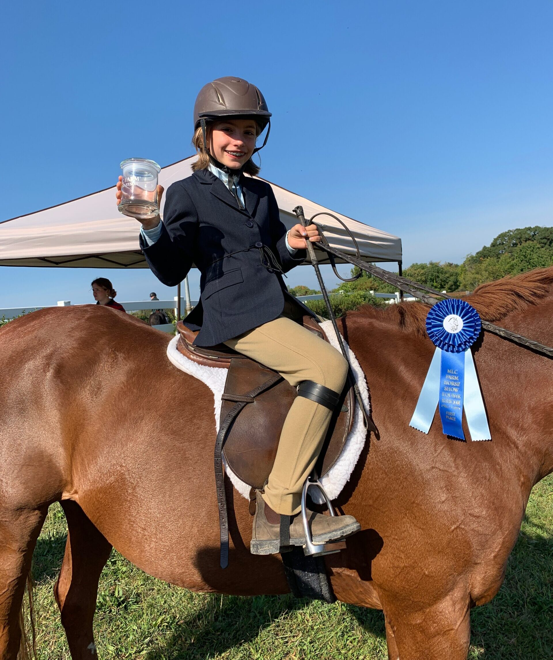 photo of young rider with ribbon and prize