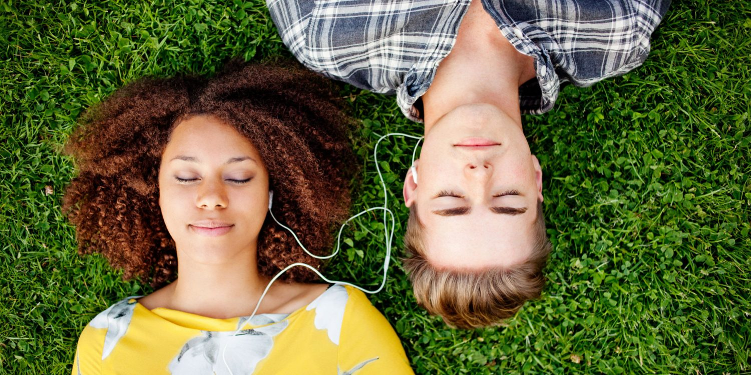Young couple listening to and sharing music.