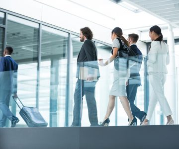 Businesspeople holding suitcase walking in office (zh translation)