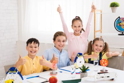Stem education. Happy children showing thumbs up and looking at camera in classroom
