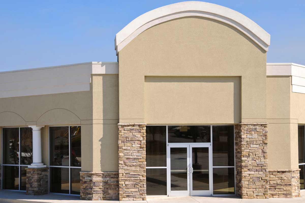 Commercial business building exterior painted dark tan and white