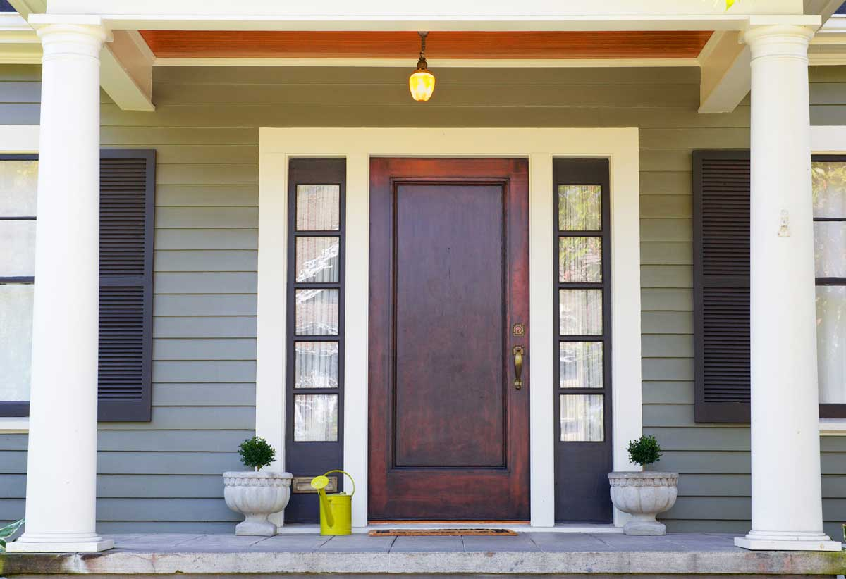 Residential home exterior front porch painted dark green, black, brown, and white