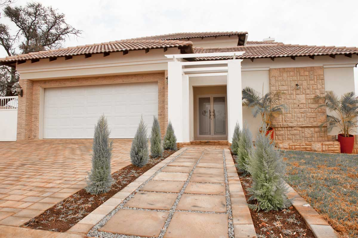 Residential home exterior painted desert tan, brown, and white